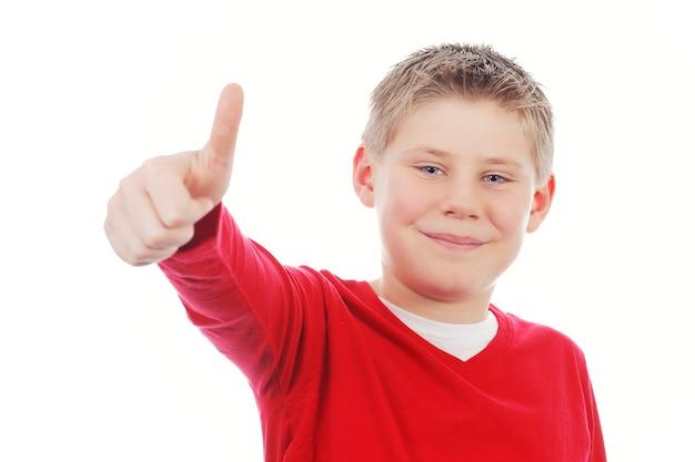 Jonge jongen die u duim geeft die omhoog op witte ruimte wordt geïsoleerd