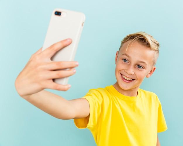 Jonge jongen die van smiley selfies neemt