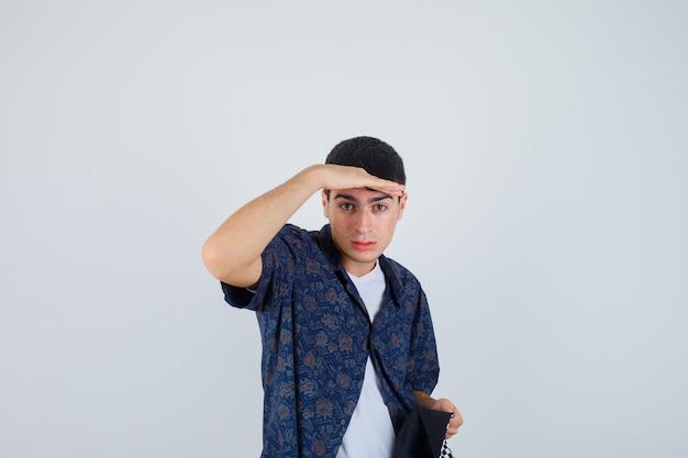 Jonge jongen die ver weg kijkt met hand boven het hoofd, pet in wit t-shirt, bloemenoverhemd, pet vasthoudt en gefocust kijkt. vooraanzicht.