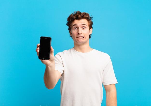 Jonge jongen die verbaasd en verward kijkt, lip bijt met een nerveus gebaar, niet wetend het antwoord op het probleem. telefoon scherm concept