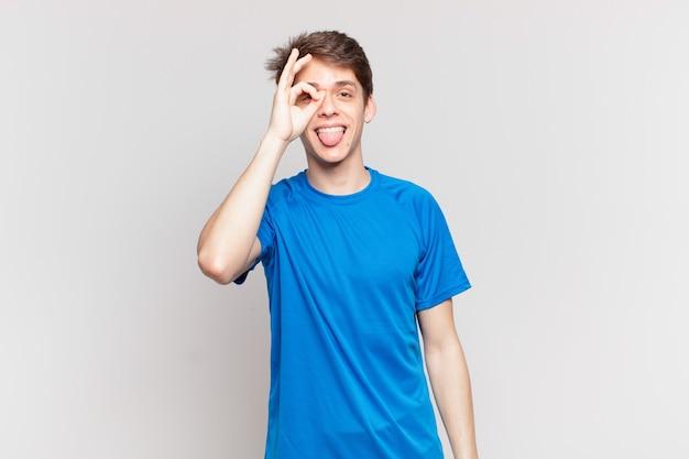 Jonge jongen die vrolijk lacht met een grappig gezicht, een grapje maakt en door een kijkgaatje kijkt, geheimen bespioneert
