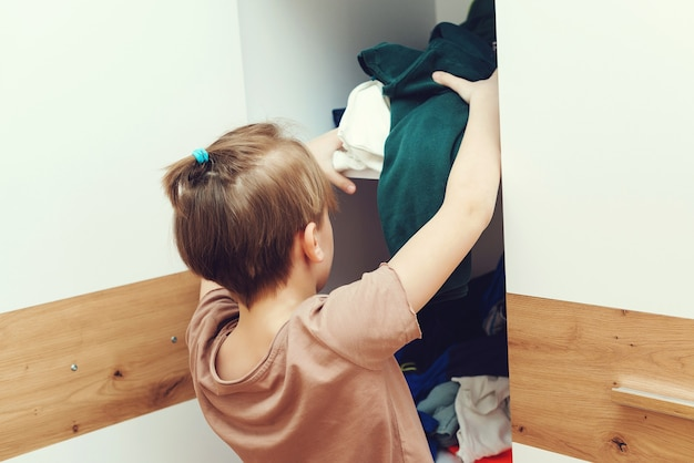 Jonge jongen die vuile kleren in kast gooit. knoeien in kledingkast en kleedkamer. slordige wanorde kledingkast. rommelige kinderkamer in huis.