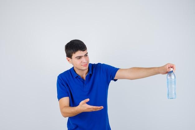 Jonge jongen die waterfles houdt, hand uitrekt zoals het presenteren in blauw t-shirt en er gelukkig uitziet. vooraanzicht.