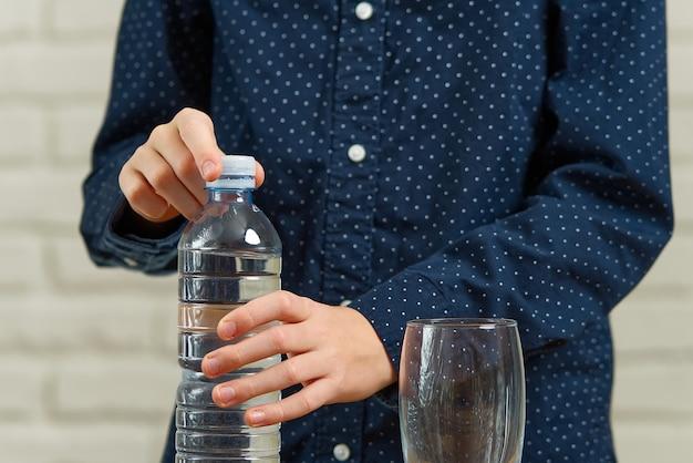 Jonge jongen die waterfles openen. jongen die fles drinkwater opent