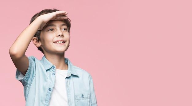 Jonge jongen die weg met exemplaar-ruimte kijkt
