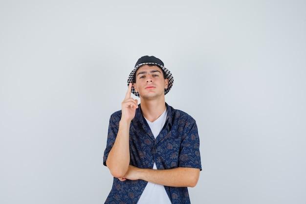 Jonge jongen die wijsvinger in eureka-gebaar opheft terwijl hij hand onder elleboog in wit t-shirt, bloemenoverhemd, pet houdt en er verstandig uitziet. vooraanzicht.