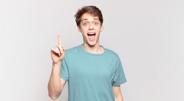 Jonge jongen die zich een gelukkig en opgewonden genie voelt na het realiseren van een idee, vrolijk vinger opsteken, eureka!