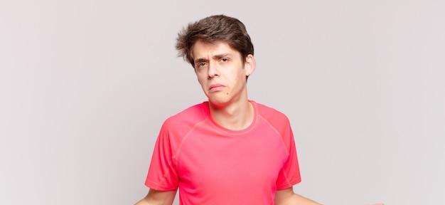 Jonge jongen die zich geen idee en verward voelt, geen idee heeft, absoluut verbaasd met een domme of dwaze blik