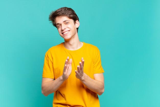 Jonge jongen die zich gelukkig en succesvol voelt, lacht en in de handen klapt, gefeliciteerd met een applaus