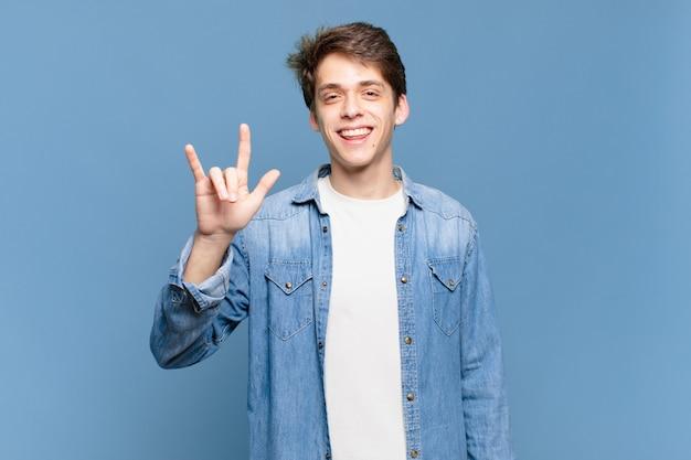 Jonge jongen die zich gelukkig, leuk, zelfverzekerd, positief en rebels voelt, rock of heavy metal met de hand tekent