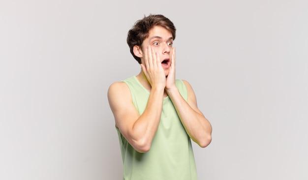 Jonge jongen die zich gelukkig, opgewonden en verrast voelt, opzij kijkend met beide handen op het gezicht
