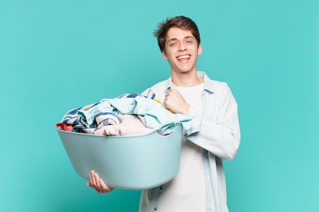 Jonge jongen die zich gelukkig, positief en succesvol voelt, gemotiveerd wanneer hij voor een uitdaging staat of goede resultaten viert bij het wassen van kledingconcept
