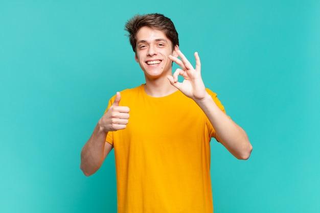 Jonge jongen die zich gelukkig, verbaasd, tevreden en verrast voelt, oke toont en duimen omhoog gebaren, glimlachend