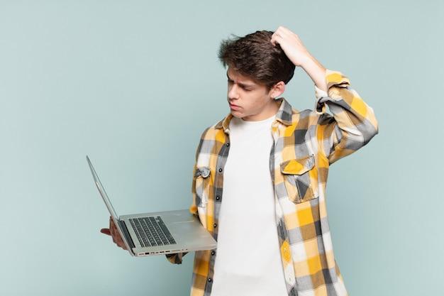 Jonge jongen die zich verbaasd en verward voelt, zijn hoofd krabt en opzij kijkt. laptopconcept