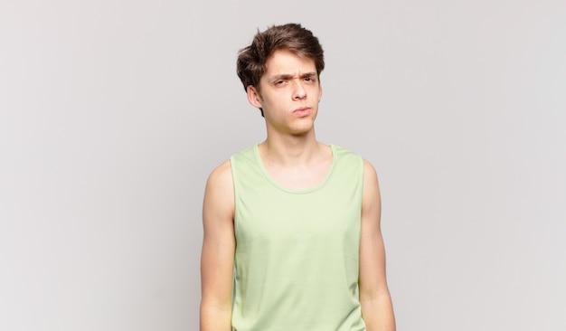 Jonge jongen die zich verward en twijfelachtig voelt, zich afvraagt of probeert te kiezen of een beslissing te nemen