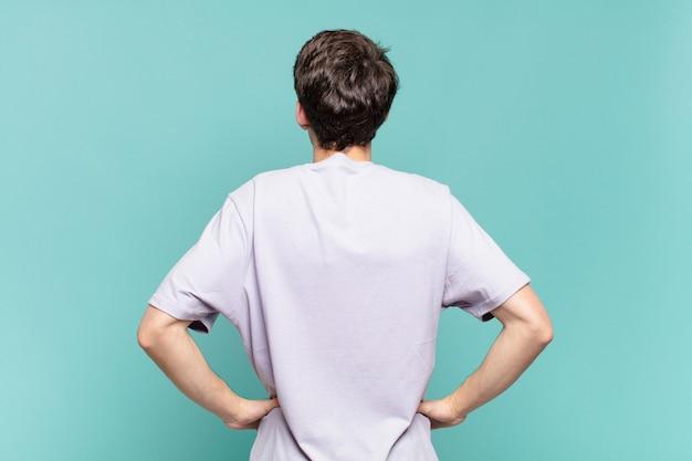 Jonge jongen die zich verward of vol voelt of twijfels en vragen, zich afvragend, met de handen op de heupen, achteraanzicht