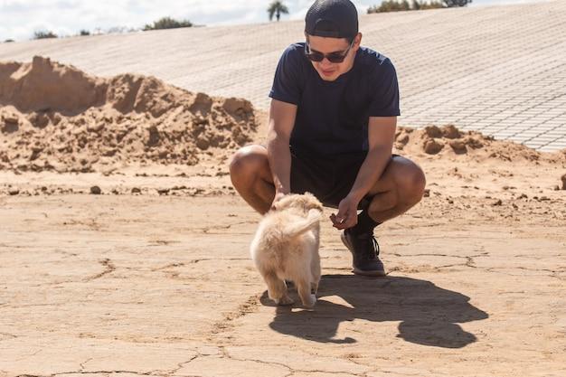 Jonge jongen die zijn puppy roept om zich bij hem in het zand aan te sluiten.