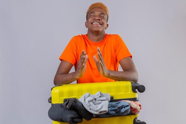 Jonge jongen draagt oranje t-shirt staan met gesloten ogen met reiskoffer vol kleren hand in hand samen met een blij gezicht over witte muur