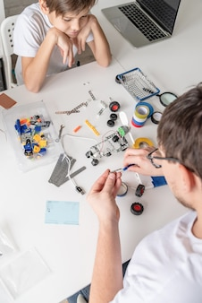 Jonge jongen en leraar plezier samen bouwen van robotauto's in de werkplaats