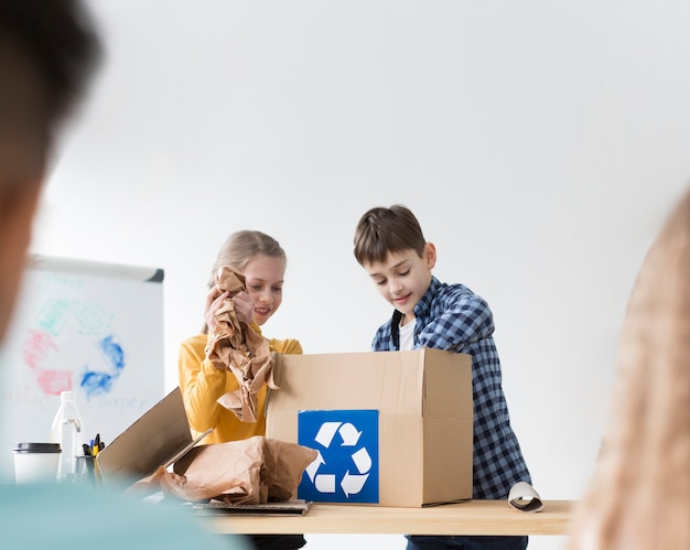Jonge jongen en meisje die leren te recycleren
