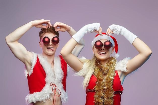 Jonge jongen en meisje in kerstman kostuums bedekten hun ogen met kerstversieringen