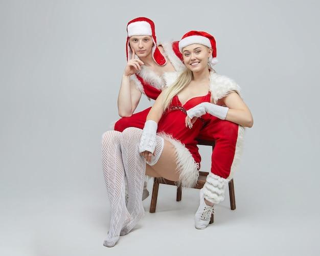Jonge jongen en meisje in kerstman kostuums. het concept van kerstmis en het nieuwe jaar. fotosessie in de studio op een witte achtergrond