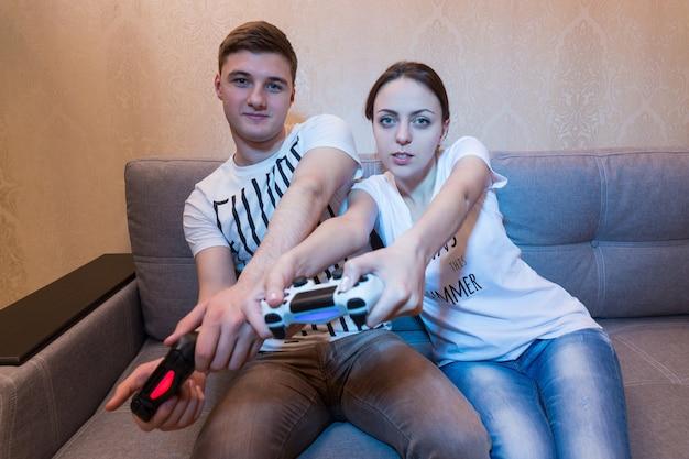 Jonge jongen en meisje zijn zo gepassioneerd door het proces van een spel dat ze zelfs de stuurbewegingen van het spel simuleren terwijl ze consoles voor zich houden terwijl ze thuis op de bank zitten