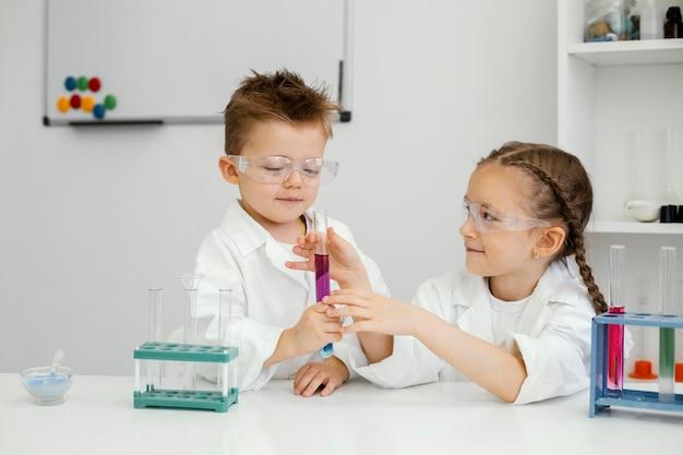 Jonge jongen en meisjeswetenschappers die experimenten in het laboratorium met reageerbuizen doen