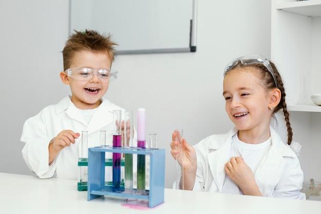 Jonge jongen en meisjeswetenschappers die pret hebben die experimenten in het laboratorium doen