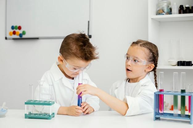 Jonge jongen en meisjeswetenschappers met reageerbuizen die experimenten in het laboratorium doen