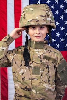 Jonge jongen gekleed als een soldaat met amerikaanse vlag