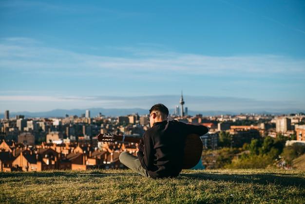 Jonge jongen gitaarspelen in de stad madrid, spanje op de achtergrond.