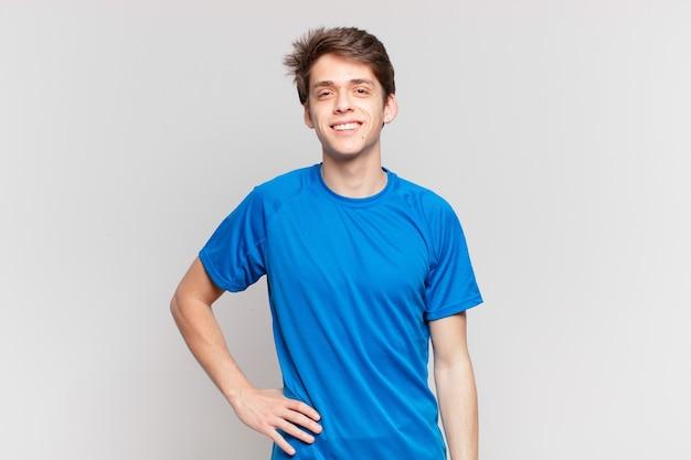 Jonge jongen glimlachend gelukkig met een hand op de heup en zelfverzekerde, positieve, trotse en vriendelijke houding