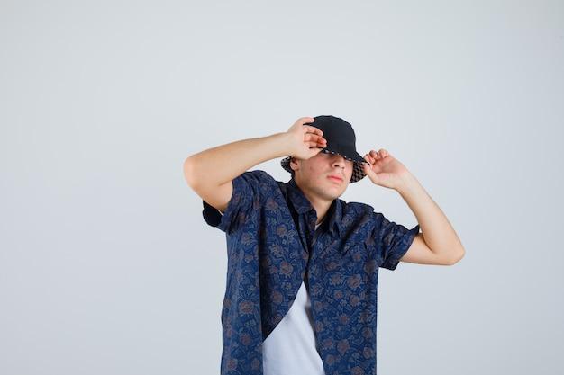 Jonge jongen handen op pet zetten in wit t-shirt, bloemenoverhemd, pet en er zelfverzekerd uitzien. vooraanzicht.