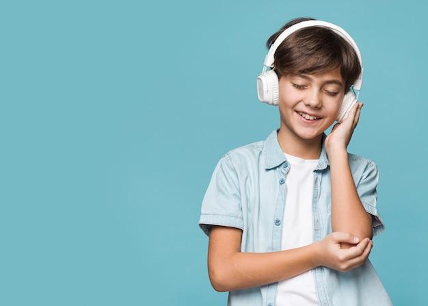 Jonge jongen het luisteren muziek met exemplaar-ruimte