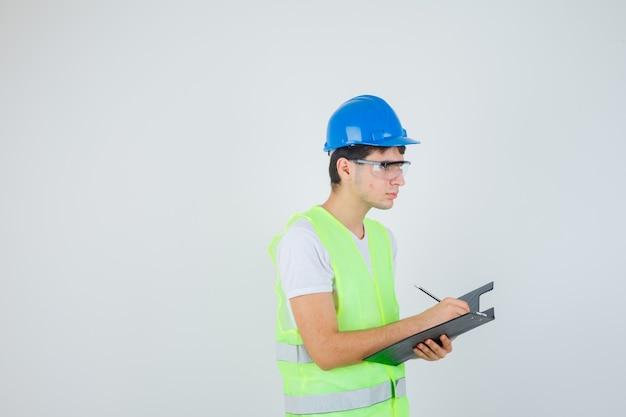 Jonge jongen in bouwuniform schrijven van notities in bestandsmap en op zoek gericht, vooraanzicht.