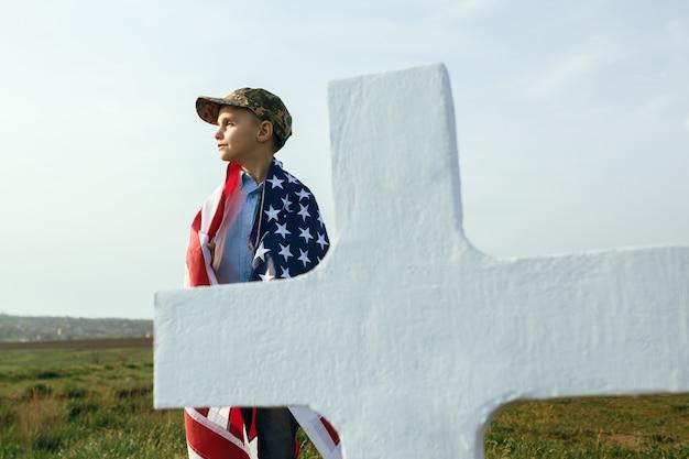 Jonge jongen in een militaire pet bij het graf van zijn vader op herdenkingsdag