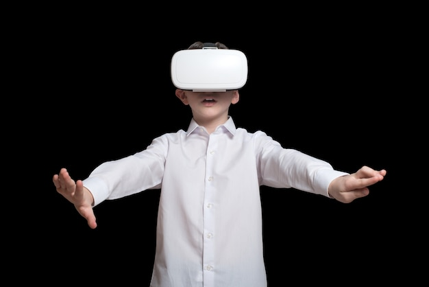 Jonge jongen in een virtual reality helm. wit overhemd. zwarte achtergrond