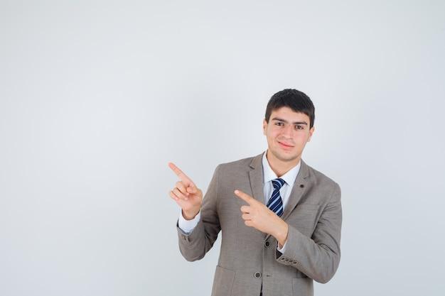 Jonge jongen in formeel pak naar links wijzend met wijsvingers en op zoek gelukkig, vooraanzicht.