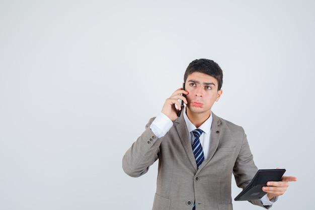 Jonge jongen in formeel pak praten met de telefoon, rekenmachine vasthouden, aan iets denken en peinzend, vooraanzicht kijken.