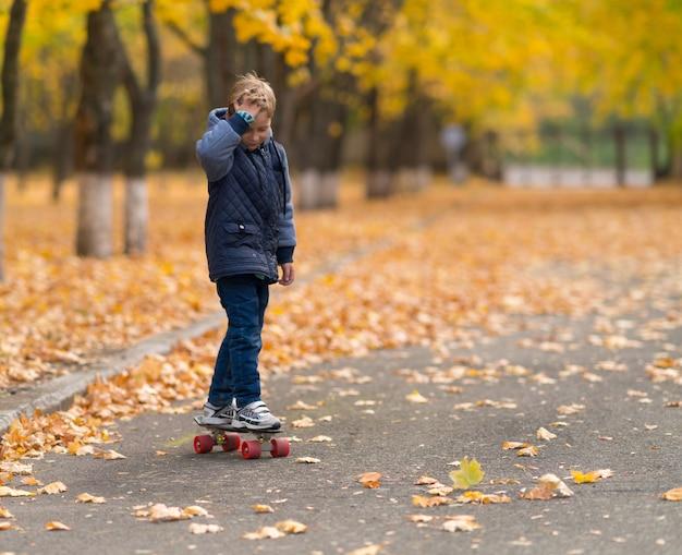 Jonge jongen in grijze jas skateboarden in het park in de herfst, gezien vanaf zijn voorkant. kopieer ruimte met wazige bomen en gele bladeren opzij.