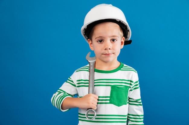 Jonge jongen in het beschermende helm stellen met moersleutel