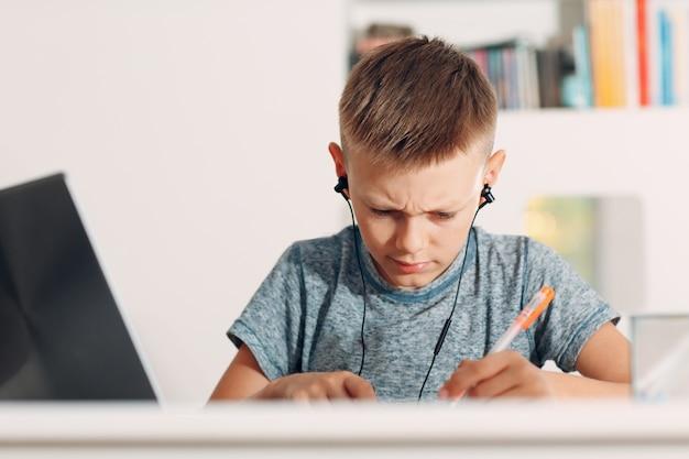 Jonge jongen in hoofdtelefoon zittend aan tafel met laptop en de voorbereiding op school thuis
