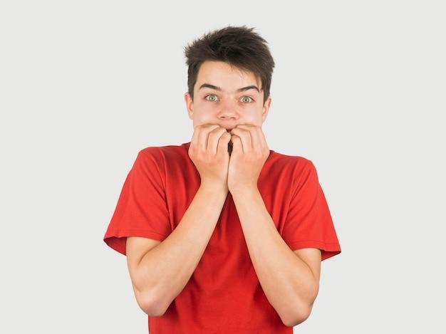 Jonge jongen in rode t-shirt die doen schrikken middelgroot schot