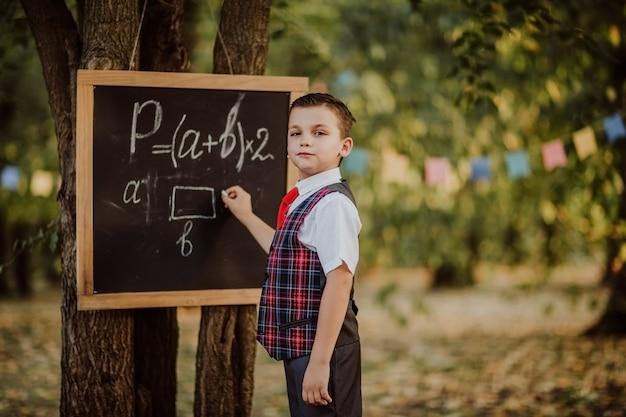 Jonge jongen in school het eenvormige schrijven op een raad door de formule van de krijtwiskunde in een park