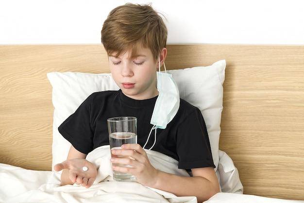 Jonge jongen in virusbescherming masker neemt pil