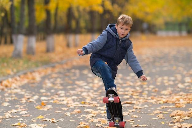Jonge jongen in warme jas doet skateboard truc gezien vanaf zijn voorkant in volle lengte op park loopbrug bedekt met gele bladeren en bomen
