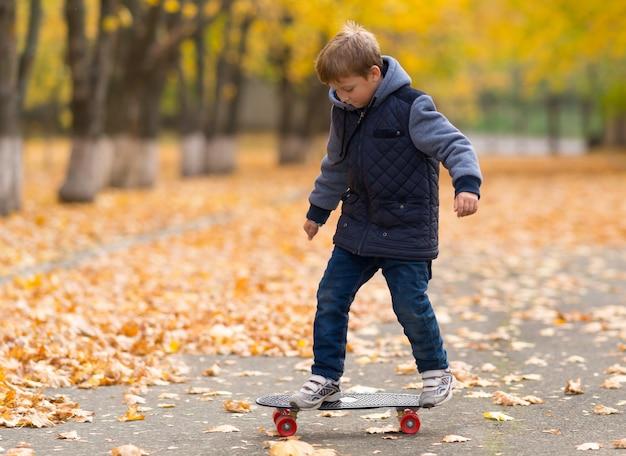 Jonge jongen in warme jas leren skateboarden, van voren bekeken over de volledige lengte, rijdend over parkpad bedekt met gele bladeren op een herfstdag
