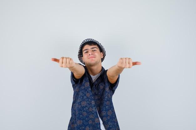 Jonge jongen in wit t-shirt, bloemenoverhemd, pet die met duimen opzij wijst en gelukkig, vooraanzicht kijkt.