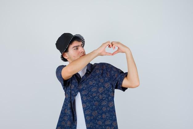 Jonge jongen in wit t-shirt, bloemenoverhemd, pet met hartgebaar en op zoek zelfverzekerd, vooraanzicht.